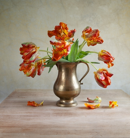Ornamental orangey-yellow tulips in an antique metal jug with fallen petals on the old wooden tabletop  photo
