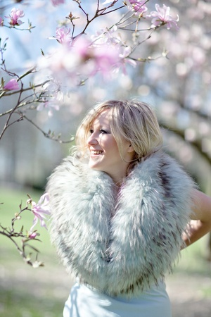 stole: Artistic photograph of a young blonde woman nestling in a fur stole standing amonst branches with blossom, high key and dreamy