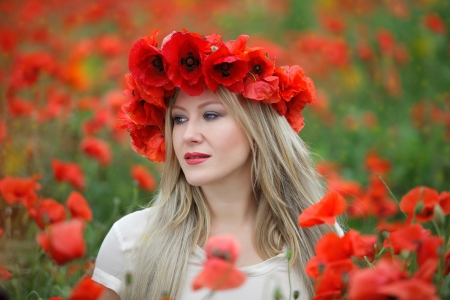 Beatiful woman in field of bright red poppy flowers in summer photo