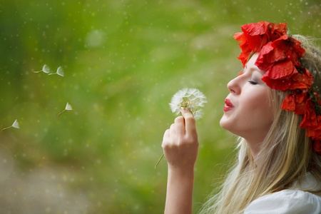 Beatiful woman with crown of poppy flowers and dandelion photo
