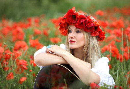Beatiful woman in field of bright red poppy flowers with Guitar photo
