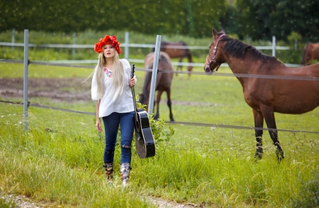 Country girl with poppy flowers and Guitar on Path with horses photo