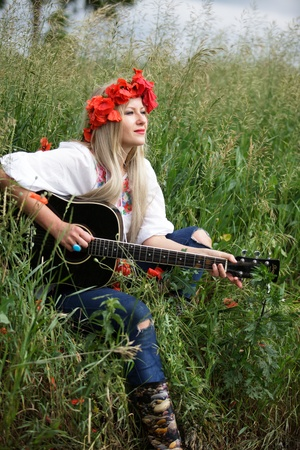 Woman with crown of poppy flowers and guitar in a meadow in summer photo