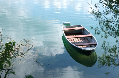 skiff: View over mirror calm lake with old row boats on a sunny summer day Stock Photo