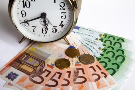 時間は、古い機械式アラーム時計とユーロ紙幣で撮影したお金の概念
