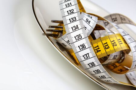 to restrain: Fork with measuring tape as a symbol of disciplined dieting and weight reduction