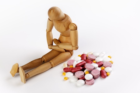 Sick puppet with stomach cramps and pile of colorful pills photo