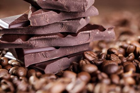 Fresh roasted coffee beans and stack of brown chocolate photo