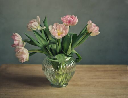 Bouquet of beautiful pastel colored pink tulips in glass vases and decorative metal basket photo