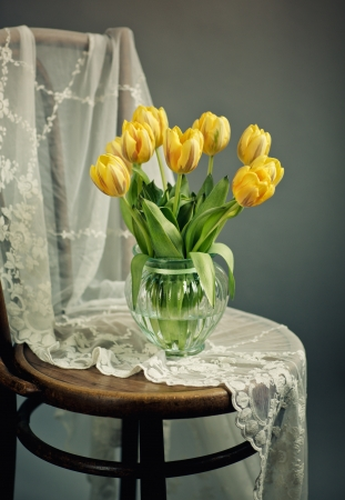 antique vase: Beautiful bright yellow tulips in Still Life in Glass Vase on antique wooden Chair with Lace Cloth