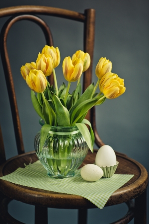 Beautiful bright yellow tulips in Still Life in Glass Vase on antique wooden Chair with fresh white Eggs photo