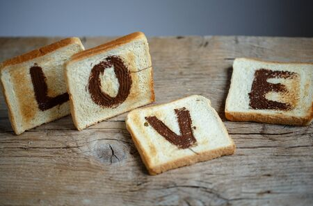 spread the word: Toast Bread with the Word LOVE painted with hazelnut chocolate spread Stock Photo