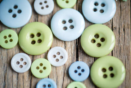 differently: Differently sized pastel colored buttons on table in soft green and blue