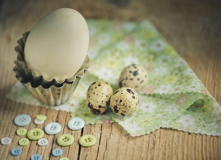 Different Eggs from Quail and Duck on table with Buttons and with small metal baking form photo