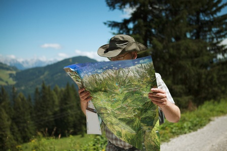 Man in Hiking gear studying a map looking for the direction while hiking in the european alps photo