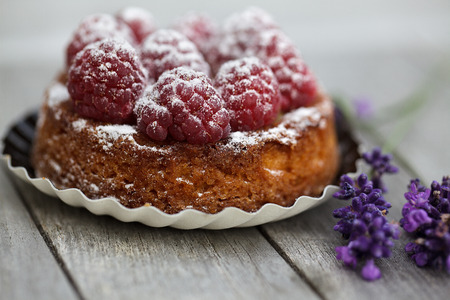 Small french Raspberry Tarte with icing sugar on wooden table photo