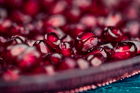 grenadine: Fresh bright red Pomegranate Grenadine seeds on glass plate on blue wooden background