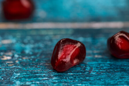 grenadine: Fresh bright red Pomegranate Grenadine seeds on blue wooden background Stock Photo