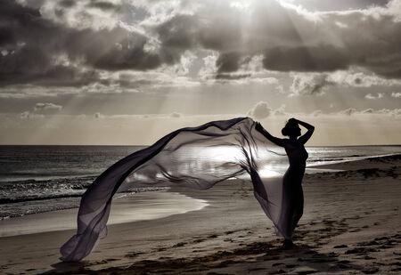 shroud: Woman on the ocean beach at Sundown as a Silhouette against the evening sky