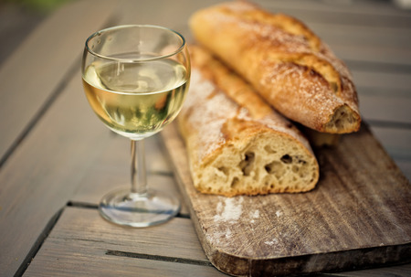 White French Bread on Wooden board with  glass of White Wine photo