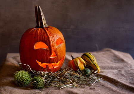 Carved red Halloween Pumpkin with Face lit by Candle inside Stock Photo