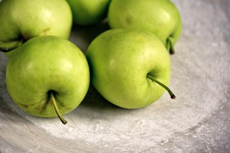 stoneware: Fresh Green Granny Smith Apples on Stoneware Plate Stock Photo