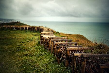 barbed wire fences: Path at the Top of the Cliffs at Fecamp Normany with wooden fence and barbed wire Stock Photo