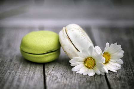 food still: Food Still Life with Macarons with Daisy Flowers on rustic wooden Table