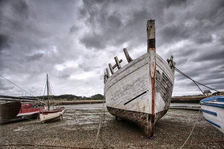 ebb: View of Old Boats in Brittany France on the shore during ebb tide