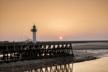 normandy: Sunset and Evening Mood at the Beach of Deauville with Pier and Lighthouse during Ebb Tide