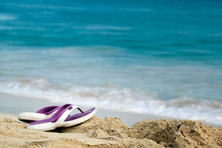Ocean Beach with Sandals on a sunny summer day Stock Photo