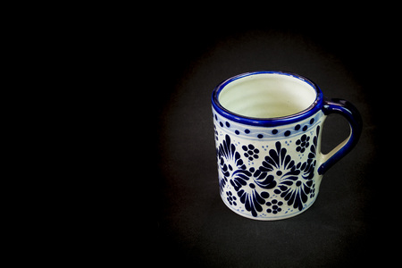 A naive cup decorated with Talavera art with a black background Editorial