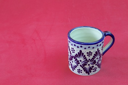 A naive cup decorated with Talavera art with a red background playing innocence Editorial