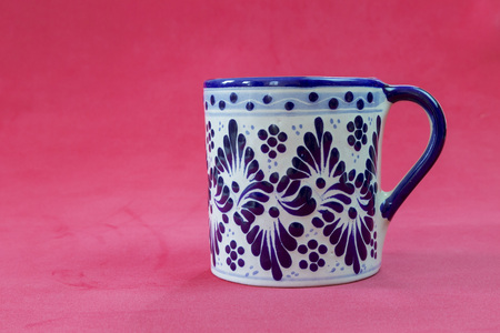 A close up of a Talavera cup with a red background in a very serious and sexy attitude Editorial