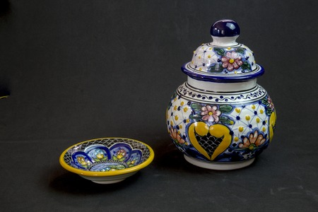 Elegance is the name of Talavera family of cute little vase and plate on a black background