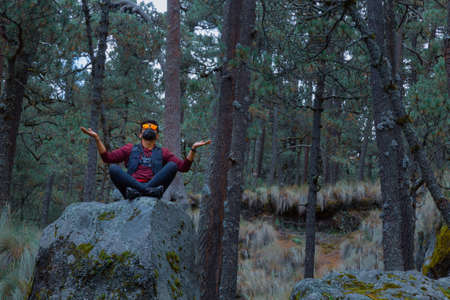 Man meditating in yoga pose wearing facial mask in nature