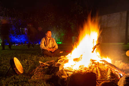 Mexican shamans meditating in front of a campfire