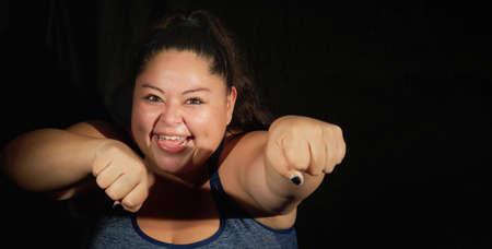 Happy overweight woman in sportswear on a black background