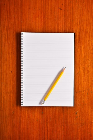 White Blank Notebook with yellow pencil on Wood Background Stock Photo