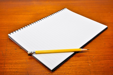 White Blank Notebook with yellow pencil on Wood Background photo