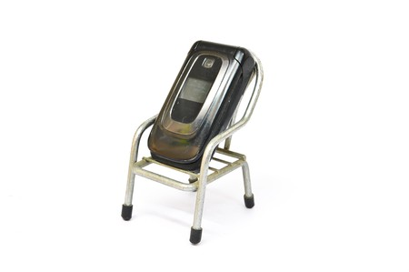 flip phone: Old Mobile Phone on small chair