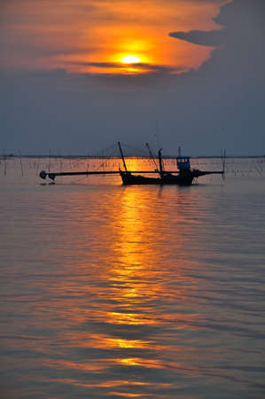 Silhouette of fishing boat in sunset over the sea photo