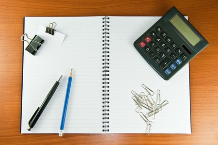 paper clip papernote notebook pen pencil and calculator photo