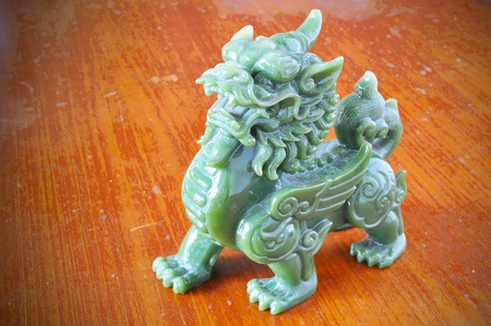 Jade Chinese Sacred Animal (call in chinese is PE-SIA) on wood background photo