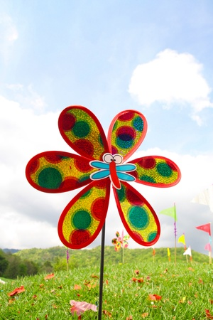 colorful windmill toy on the grass with bluesky photo