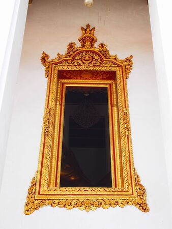 dimming: Golden stucco window frame seeing golden Buddha in the dark dimming frame. Thai ancient syle architecture. Editorial