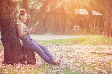 Young woman asian using digital tablet in the park. Stock Photo