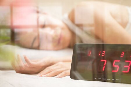 Alarm clock in front of asian girl on the bed. Stock Photo