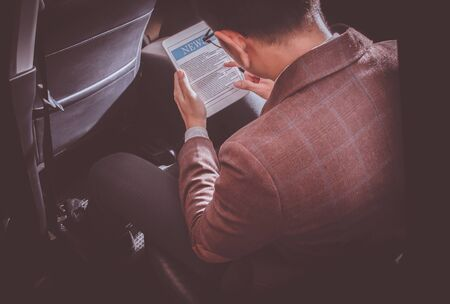 Businessman sitting in the back seat of the car with a tablet