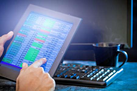 Man using tablet, Stock market data